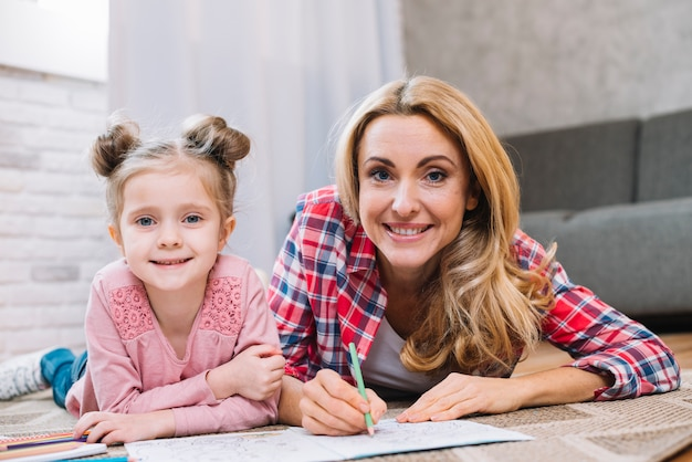 Portrait of beautiful woman with little girl drawing in home