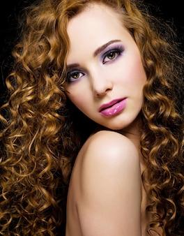 Ritratto di una bella donna con lunghi capelli ricci