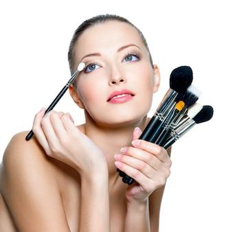 Ritratto di una bella donna con i pennelli trucco vicino al viso attraente.
