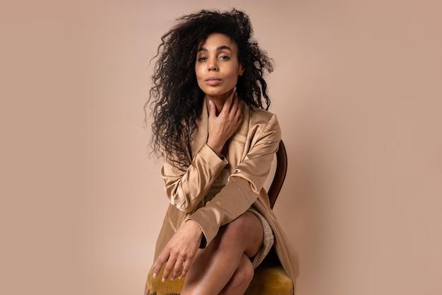 Ritratto di una bella donna con capelli ondulati perfetti in una giacca lucida dorata
