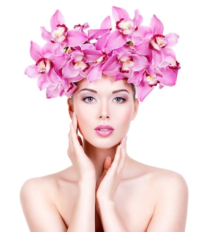 Portrait of  beautiful woman with a pink flowers. pretty adult girl with healthy skin of a face.  - isolated on white wall