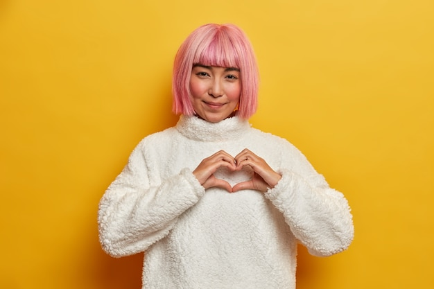 Portrait of beautiful woman with pink short hair, shapes heart gesture, expresses love to someone, confesses in sympathy, shares romantic feelings