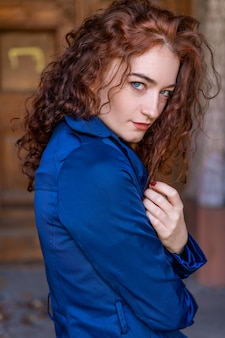 Portrait of beautiful woman with red hair in blue cloak