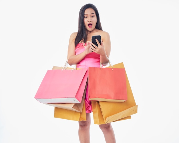 Portrait of beautiful woman with shopping bags and smartphone on white surface, space for text