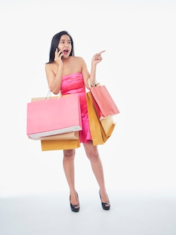 Portrait of beautiful woman with shopping bags and talking on phone on white surface, space for text