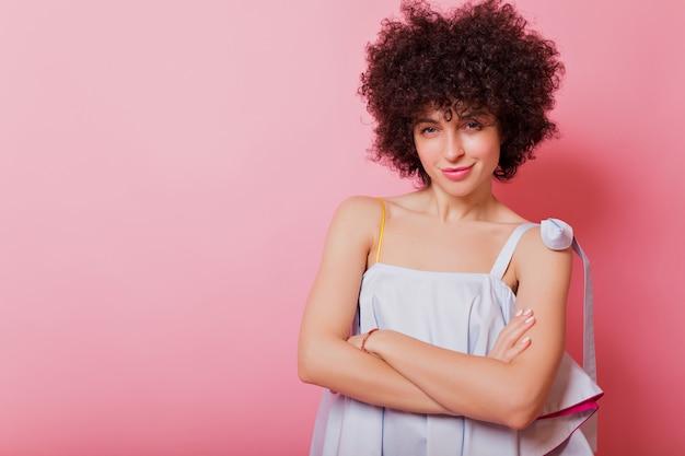 Ritratto di bella donna con capelli ricci corti e grandi occhi azzurri pone in rosa con un bel sorriso