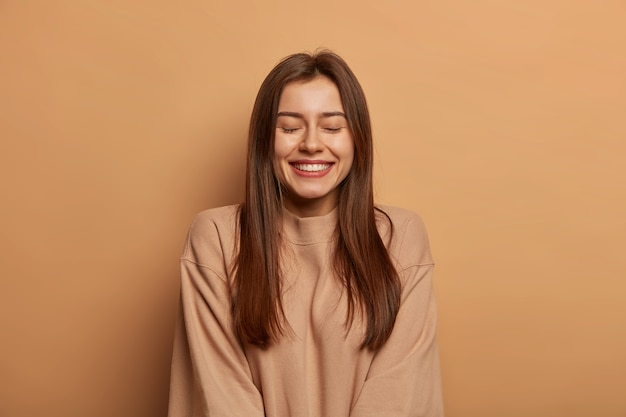 Portrait of beautiful woman with straight dark hair, smiles broadly, keeps eyes shut, enjoys pleasant moment