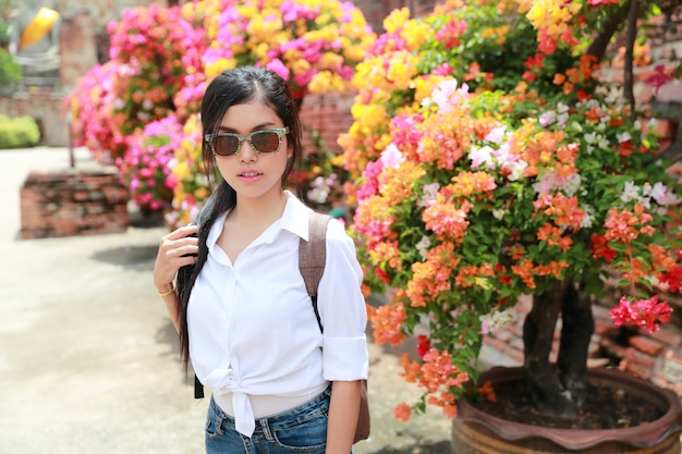 Portrait of beautiful woman with sum glasses having a happy time and enjoying among flowers in temple