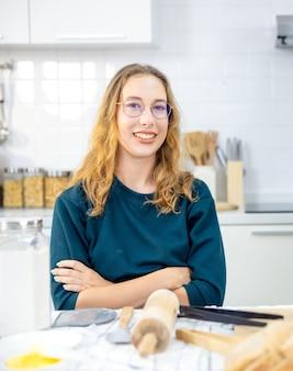 Портрет красивой женщины с инструментами, выпеченными на кухне