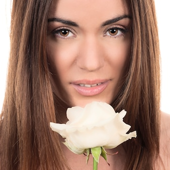 Ritratto di bella donna con rosa bianca su sfondo bianco