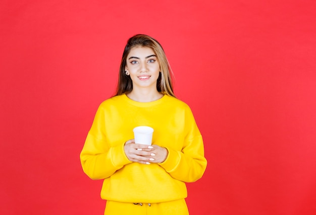 Portrait of beautiful woman in yellow outfit posing with cup of tea