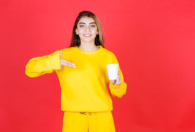 Portrait of beautiful woman in yellow outfit standing with cup of tea