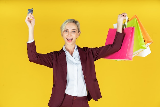 Portrait of beautiful women holding shopping bags with credit card and enjoying shopping on yellow