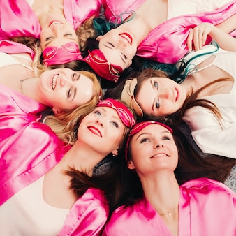 Portrait of beautiful women in pink robes celebrating bridal shower.