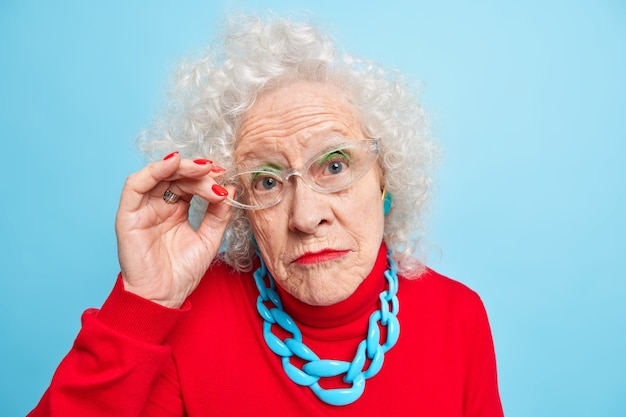 Portrait of beautiful wrinkled senior woman has curly grey hair bright makeup manicure looks attentively through transparent glasses wears red jumper and necklace