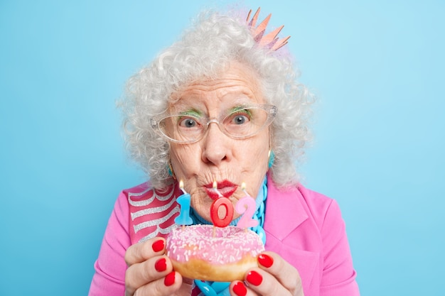Portrait of beautiful wrinkled woman holds glazed doughnut with candles celebrates 102nd birthday looks brilliant wears makeup has red nails