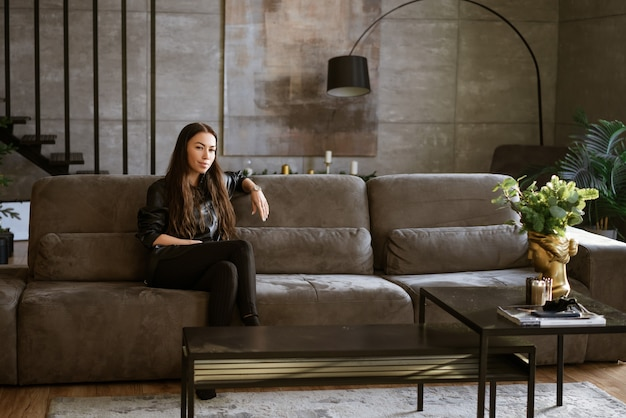 Portrait of a beautiful young adult brunette woman sitting on the sofa in the living room the girl i...