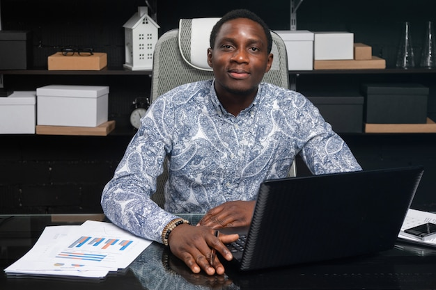 Portrait of beautiful young african american businessman working with documents and laptop in office
