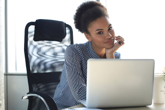 Portrait of beautiful young african american woman working with laptop while sitting at the table.