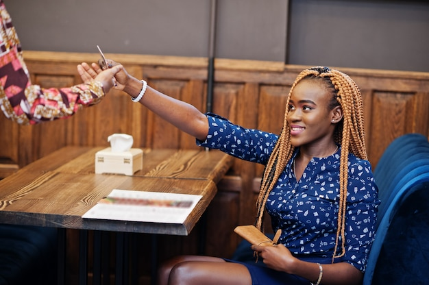 Portrait of beautiful young african business woman, wear on blue blouse and skirt, sitting at restaurant and gives credit card to waiter afro girl.