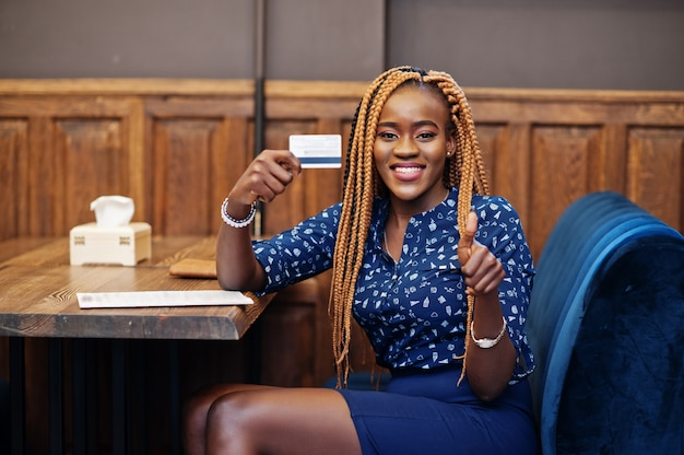 Portrait of beautiful young african business woman, wear on blue blouse and skirt, sitting at restaurant and hold credit card in hand. she show thumb up.