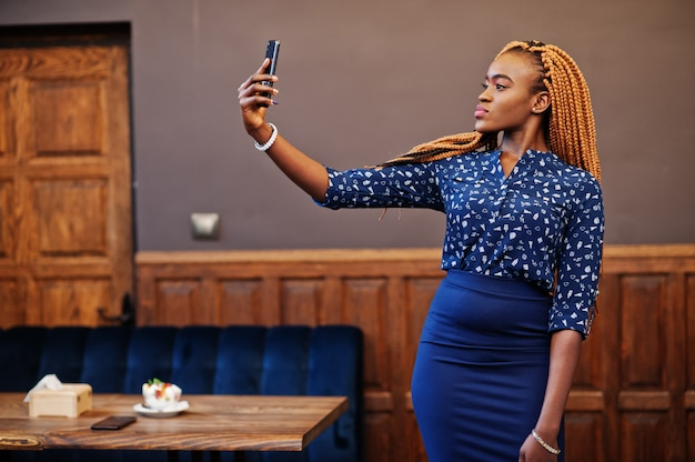 Portrait of beautiful young african business woman with dreadlocks, wear on blue blouse and skirt, posed in cafe and making selfie on phone.