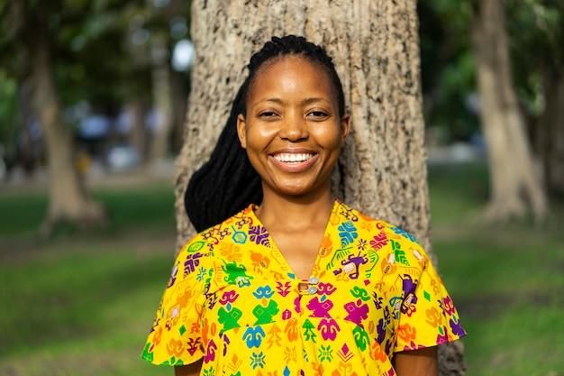 Улыбка портрета красивая молодая африканская женская с зеленой предпосылкой