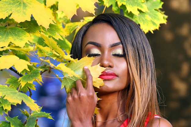 Portrait of beautiful young african woman on autumn leaves background