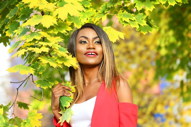 Portrait of beautiful young african woman on autumn leaves space