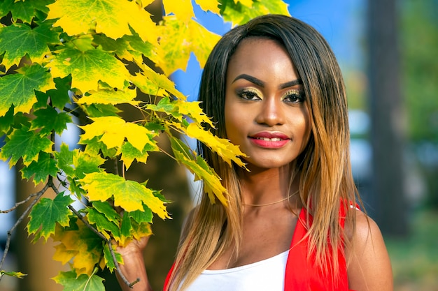 Portrait of beautiful young african woman on autumn leaves