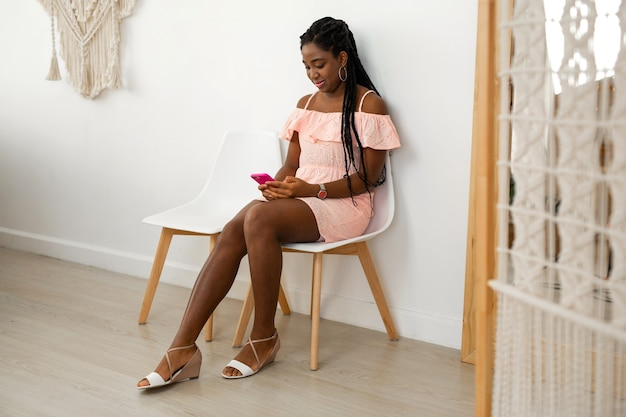 Portrait of beautiful young african woman in dress with mobile phone on chair