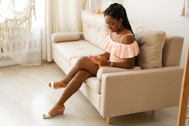 Portrait of beautiful young african woman in dress with mobile phone on sofa