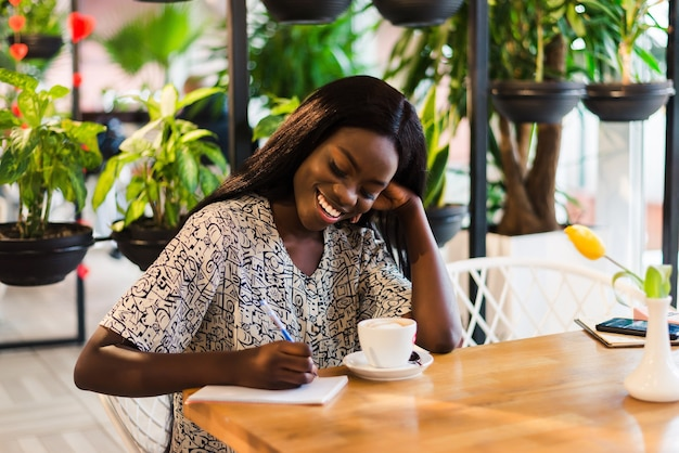 Portrait of beautiful young african woman sitting at cafe and writing notes