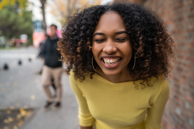 Portrait of beautiful young afro-american confident woman laughing in the street. outdoors.
