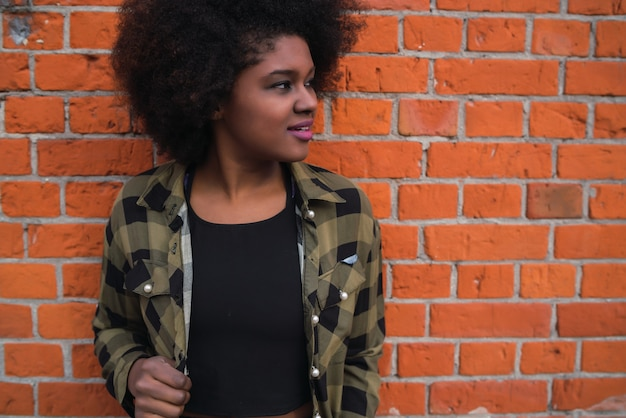 Portrait of beautiful young afro american latin woman with curly hair standing against brick wall.