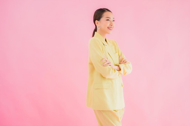 Portrait beautiful young asian business woman smile in action on pink color