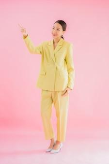 Улыбка бизнес-леди портрета красивая молодая азиатская в действии на розовом цвете