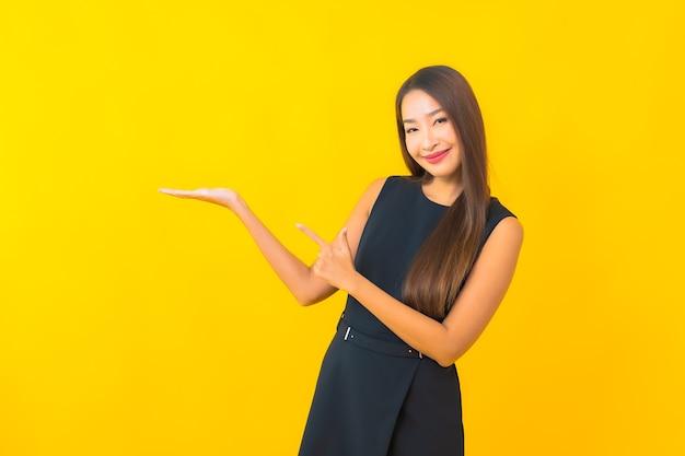 Улыбка бизнес-леди портрета красивая молодая азиатская с действием на фоне желтого цвета