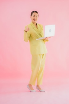 Portrait beautiful young asian business woman use computer laptop on color