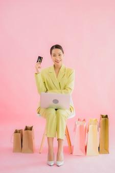 肖像画の美しい若いアジアビジネス女性の色でコンピューターのラップトップを使用します。