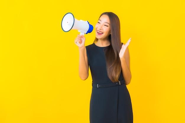 肖像画美しい若いアジアのビジネスウーマンは、通信にメガホンを使用