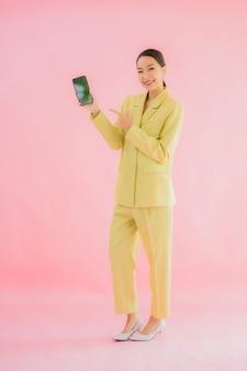 肖像画の美しい若いアジアビジネスの女性は色のコーヒーカップを持つスマートな携帯電話を使用します。