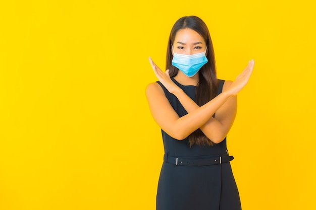 Portrait beautiful young asian business woman wear mask for protect covid19 on yellow background