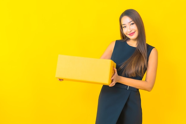 Portrait beautiful young asian business woman with brown box ready for shipping on yellow background