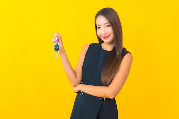 黄色の背景に車のキーと肖像画美しい若いアジアのビジネス女性
