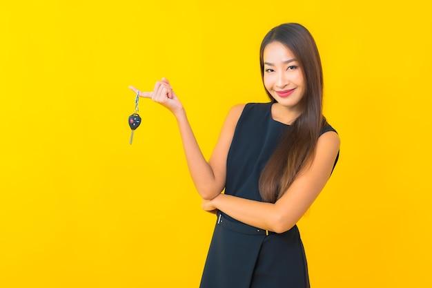 노란색 배경에 자동차 키와 세로 아름 다운 젊은 아시아 비즈니스 우먼