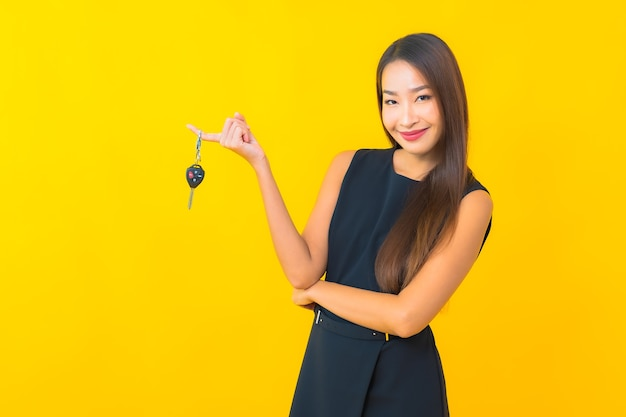 Portrait beautiful young asian business woman with car key on yellow background