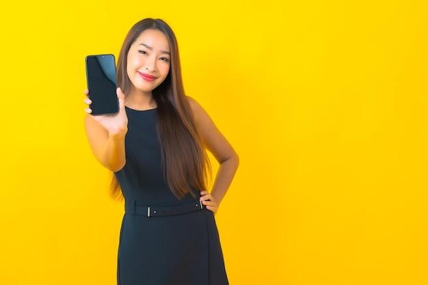 Bella giovane donna asiatica di affari del ritratto con la tazza di caffè e il telefono cellulare astuto su fondo giallo