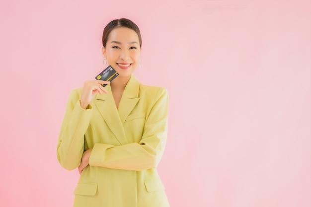 Bella giovane donna asiatica di affari del ritratto con la carta di credito sul colore