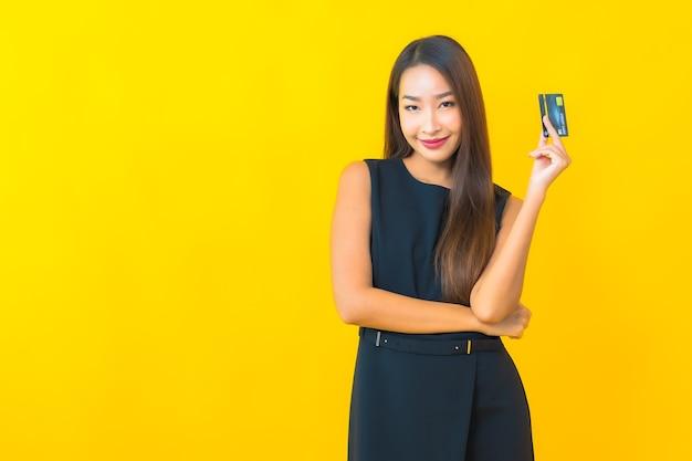 黄色の背景にクレジットカードを持つ美しい若いアジアのビジネス女性